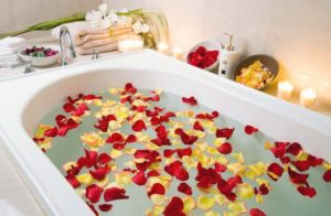 bath filled with red and yellow flower petals and with candles nearby