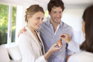 young couple taking house keys from real estate agent