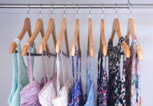 multiple female tops on hangers in a closet