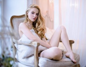 blonde woman sitting in chair with nudity obscured by pillows