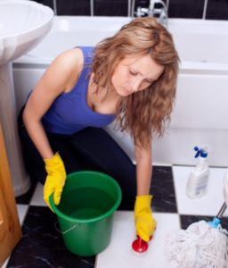 woman in blue top on her knees scrubbing bathroom floor