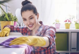 woman in plaid shirt and yellow gloves cleaning a well-lit room