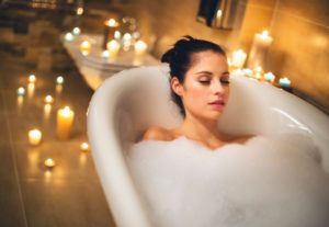 woman having a bubble bath with multiple candles in background