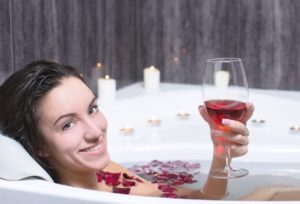 woman in bath holding up glass of red wine