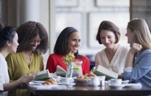 five women discussing book at a table
